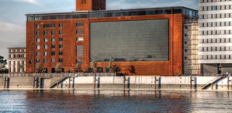 Direkt am Rheinufer gelegen, erhebt sich der Speicher 7 im Mannheimer Hafengebiet mit rostroter Hülle und vertikal in die Fassade integrierter Photovoltaikanlage.