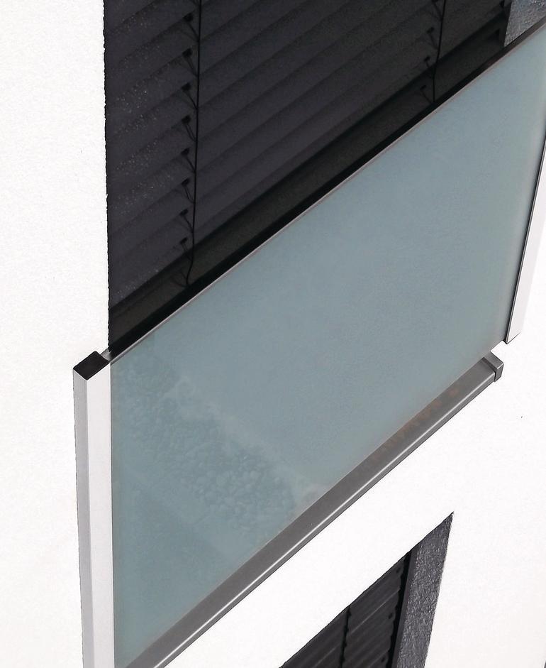 Absturzsicherung aus grauem Milchglas vor einem bodentiefen Schwenkfenster. Bild: Gutmann