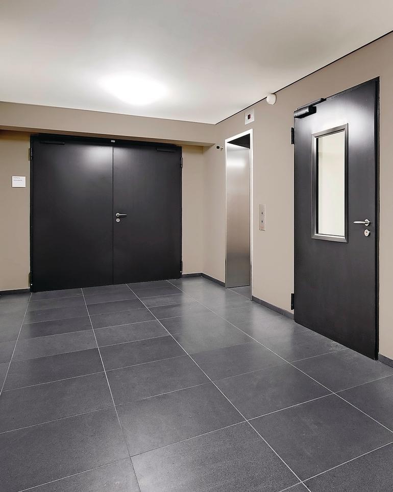 Flur mit auf den Fliesenboden farblich abgestimmten Türen. Bild: Novoferm