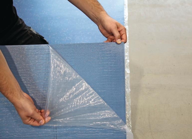 Die durchsichtige SChutzfolie wird vom blauen Dämmstoff abgezogen. Bild: nora