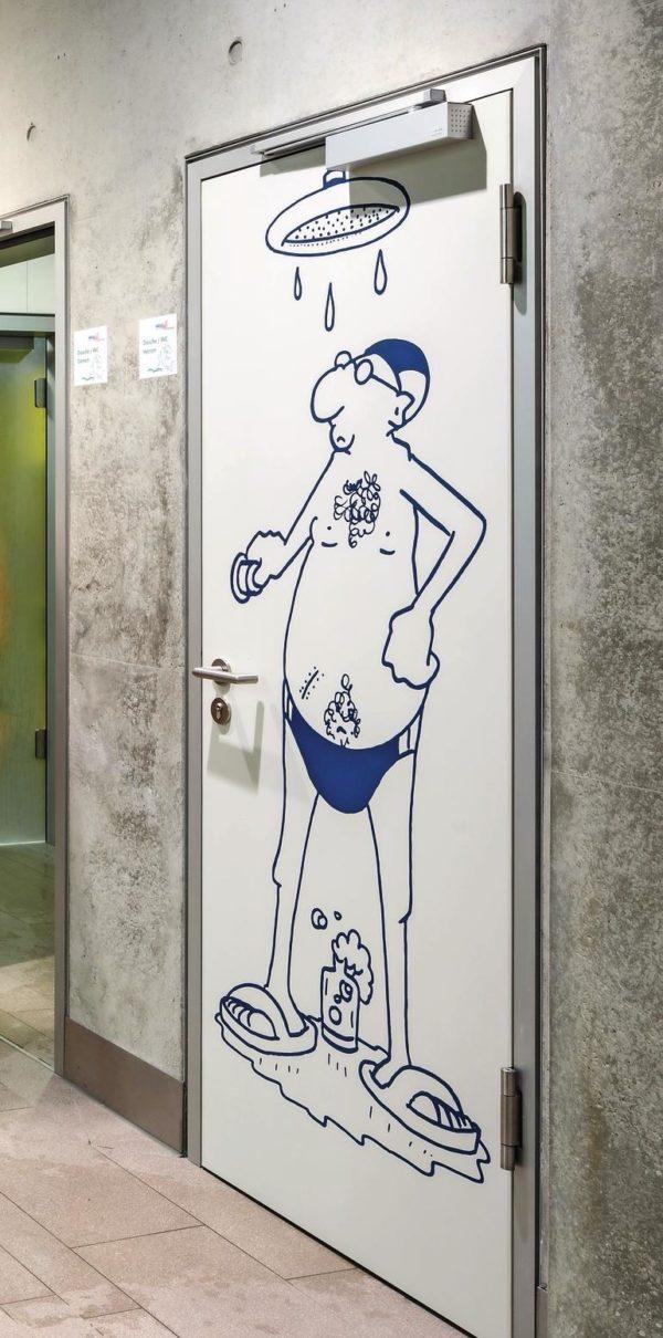Türe einer Dusche in einem öffentlichen Schwimmbad zeigt mit einer Comiczeichnung die Geschlechtertrennung an. Bild: Küffner/Gericke