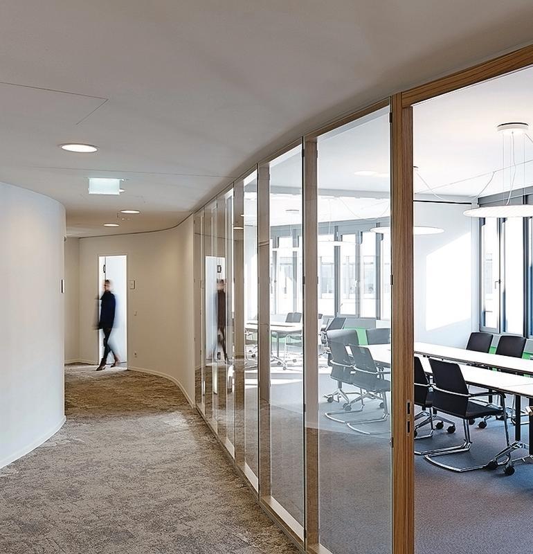 Eine Glastrennwand mit dünnen Holzprofilen trennt den Konferenzraum vom Flur ab. Bild: Strähle