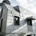 Die Aluminiumpaneele an Dach und Fassade ergänzen durch ihre heterogene Oberfläche die skulpturale Form des Hauses.
