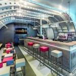 Die Cargo-Bar wurde wie der aufgeschnittene Rumpf eines Transportflugzeugs gestaltet. Bild: AEG