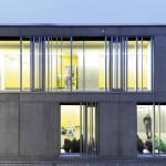 Auf der Gebäuderückseite ermöglichen Öffnungen in den Sichtbetonwänden Einblicke. Bild: Liebel/Architekten