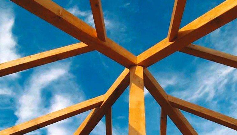 Dachpfeiler aus Holz vor einem leicht bewölkten Himmel. Bild: KVH