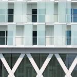 Die vorgelagerten, rhythmisch angelegte Tafeln kontrastieren mit der X-förmigen Fassadenstruktur des zweigeschossigen Sockels. Bild: Lumecore – Toon Grobet