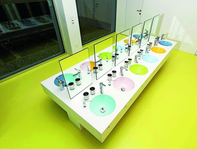 Langgezogener Waschtischbereich in hellen Farben mit 12 farblich unterschiedlichen Becken. Bild: Claudio Bader, Lugano