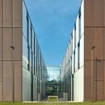 Blick zwischen zwei Gebäuderiegel auf die gläserne Magistrale. Bild: Zooey Braun