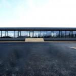 Einstöckiges Bürogebäude in Form eines liegenden Quaders mit eingerückten Glaswänden an den schmalen Längsseiten. Bild: Ott Architekten