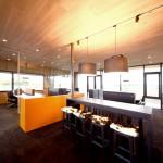 Büroräume mit dickem Teppichboden und niedriger hölzerner Decke erzeugen eine gemütliche Atmosphäre. Bild: Ott Architekten