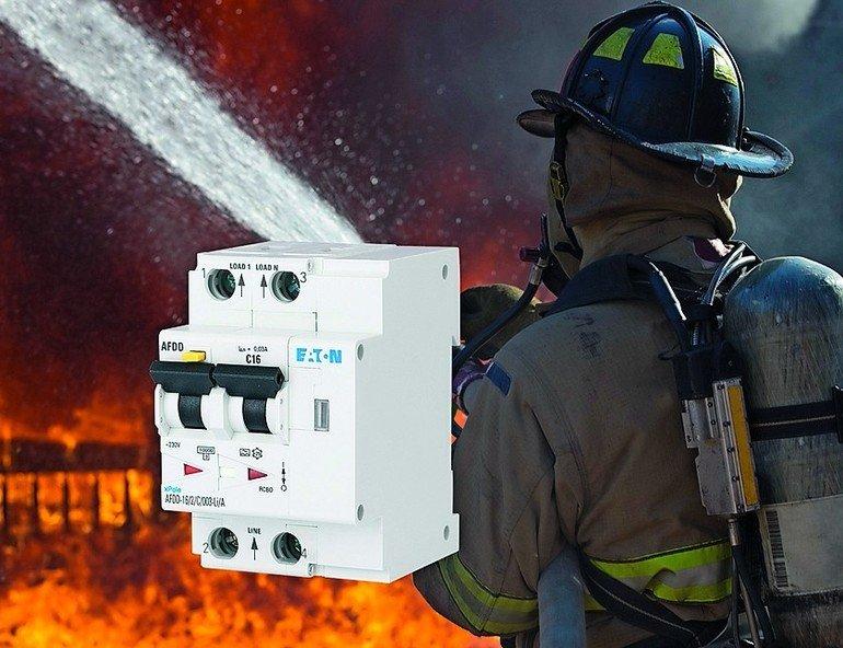 Zwei Sicherungsschalter vor dem Bild eines Feuerwehrmanns, der einen Brand löscht. Bild: Eaton