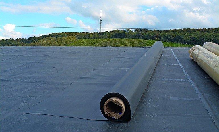 Eine halb abgerollte Dachplane auf einem Flachdach. Im Hintergrund Weinberge und der Stuttgarter Fernsehturm. Bild: Firestone Building Products