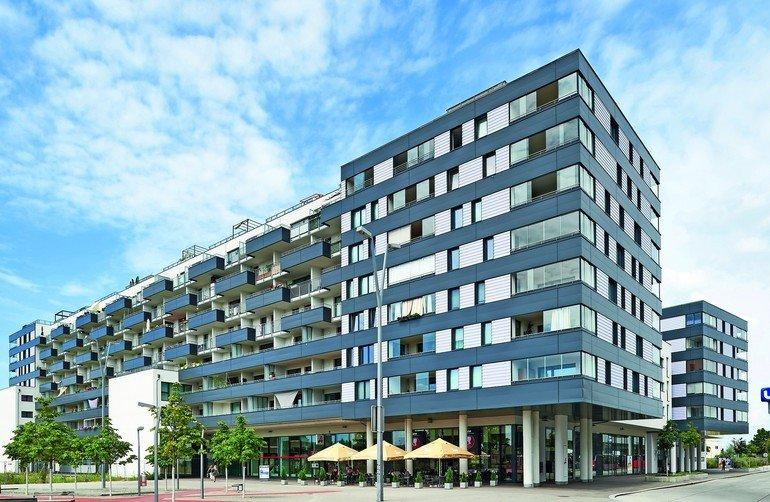 An einem Wohngebäude in Wien bieten flexible Glas-Faltwände als Loggiaverglasungen Schutz vor Straßenlärm und schaffen zugleich lichte Freiräume.