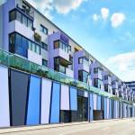 Die farbig gestalteten Stahlbetonfertigelemente der Garagen im EG und 1. OG verleihen der Fassade in Kombination mit den weiß verputzen Flächen Rhythmus. Bild:Solarlux