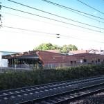 Zur Bahnlinie hin ist der Baukörper geschlossen, während er sich zum Garten hin mit einer großzügigen Verglasung öffnet. Bild: Michael Schnell