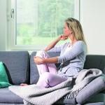 Frau sitzt auf Sofa und schaut aus dem Fenster. Bild: Rehau AG + Co