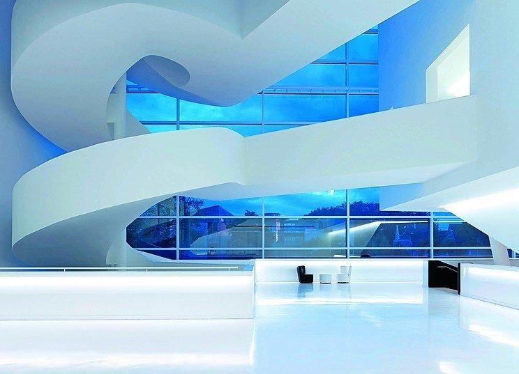 Eine Lobby mit fugenlosem Hochglanzboden, darüber scheinbar freischwebende Laufwege und Treppen. Bild: Brillux