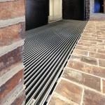 Die Schlitzrinnen des Typs Lamina passen sich im Pflaster dem linierten Fußabtritt vor dem Ausgnag bzw. dem Zugang zu dem Veranstaltungsraum an, so dass sie nahezu unsichtbar erscheinen. Bild: Richard Brink GmbH & Co. KG