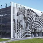 Lamellen an der Fassade eines Parkhauses zeigen von der Seite betrachtet eine Gruppe Zebras.Bild: Goldbeck GmbH