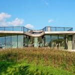 Die Panoramafront lässt sich flexibel öffnen und bietet vom Wohn- und Essbereich aus eine weite Aussicht über den schilfbewachsenen Garten zur angrenzenden Polderlandschaft. Bild: Fedde de Wert