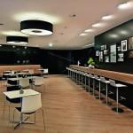 Auch im Gastrobereich des Messestandes harmoniert technisch-kühles Schwarz mit einem warmen Holz-Farbton. Bild: Andreas Keller, keller-fotografie.de