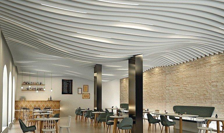 Eine Cafeteria mit geschwungener Lamellendecke und einer Wand im Natursteinlook. Bild: Lindner-Group