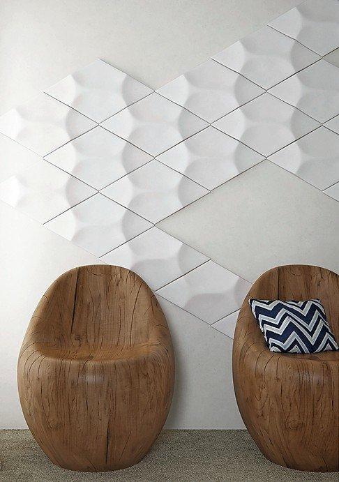 Zwei monolithische Holzsessel vor einer Wand mit weißen Dekokacheln. Bild: NMC