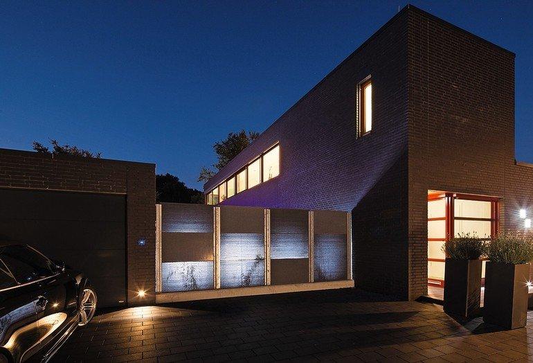 Hell erleuchtetes Haus mit Klinkerfassade in der Abenddämmerung. Bild: Lucem