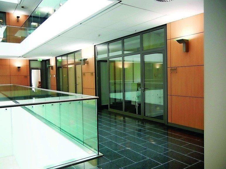 Flur eines Bürobaus mit Glasgeländer zum innenliegendem Atrium. Bild: Sälzer