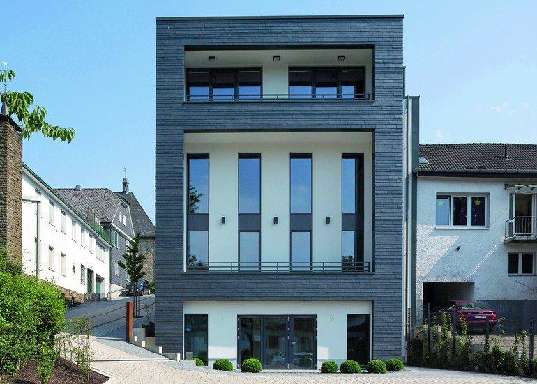 Rückseite eines viergeschossigen Geschäftshauses mit Schiefer- und Putzfassade. Bilder: Rathscheck Schiefer