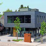Das von der Straßenfront zurückversetzte Gebäude formt einen kleinen Platz mit Bäumen. Bild: Rathscheck Schiefer