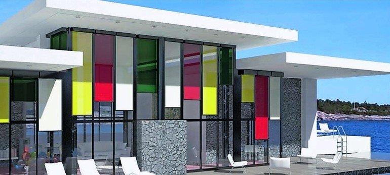 Haus mit Stein- und Glasfassade und bunten Markisen. Bild: Alukon