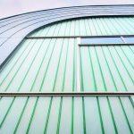 Organisch geformt, umfasst das Metallband die lichtdurchlässige und lichtstreuende Profilglasfassade. Bild: Tibor Zsitva