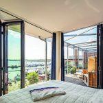 Selbst vom Bett aus lässt sich dank der transparenten und leichtgängigen Glas-Faltwände die Aussicht bequem genießen. Bild:Solarlux GmbH