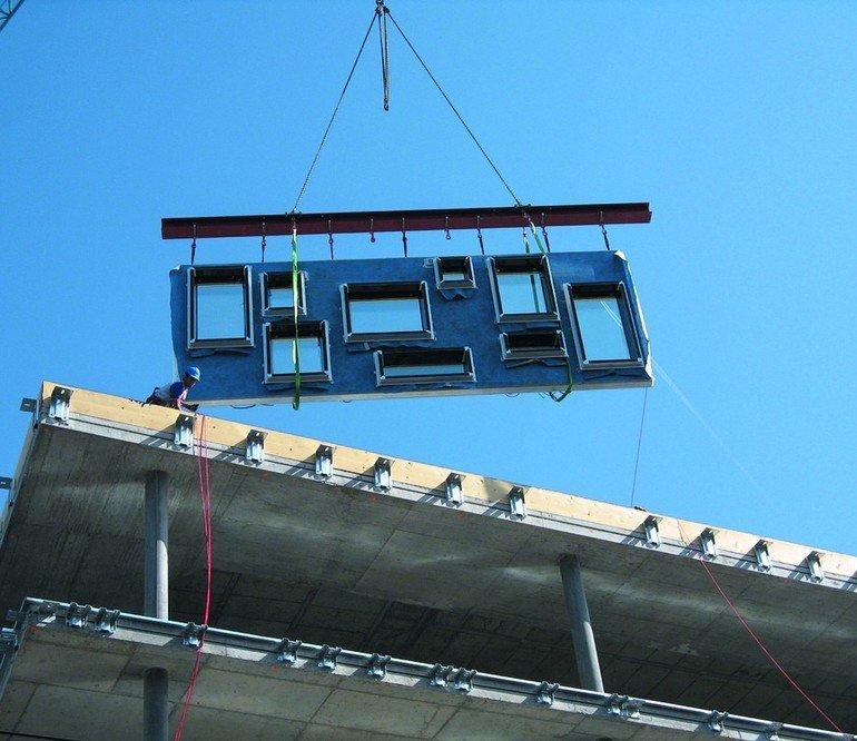 Wandelement mit vormontierten Fenstern wird an seinen Platz gebracht. Bild: Cocoon System AG
