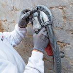 Das gereinigte Mauerwerk wird für optimale Haftvermittlung abgeschliffen. Der Schlauch des Schleifgerätes sorgt dafür, dass der Innenraum möglichst wenig mit Staub belastet wird. Bild:Isotec