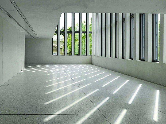 Großer Raum mit Sichtbetonoberflächen und vielen Fenstern. Bild: Stefan Müller
