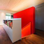 Über eine einläufige Treppe entlang der roten Wand führt der Weg neben dem Mittelunterzug ins Obergeschoss. Bild: Klimaholzhaus | Lignotrend | Fotograf Frank Brüderli, Stallikon