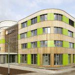 Eine gebäudehohe Pfosten-Riegel-Konstruktion aus Brettschicht-Holz markiert den Haupteingang. Bild: Ulrich Hoppe