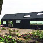 Geradlinig modern erscheint das Gebäude von der Gartenseite her – nicht zuletzt dank der tiefschwarzen Außenhaut. Bild:Lilly Jencks Studio