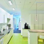 Die Decke der Teeküche folgt der Gestaltung der Arbeitsräume, greift aber mit Leuchten von Tobias Grau auch noch ein Motiv des Kundencenters auf. Bild: Owa