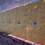 Dämmplatten hinter einer Ziegelmauer. Bild: Ursa