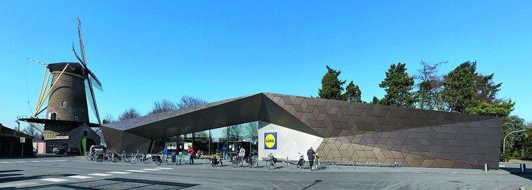 In Dongen (Niederlande) wurde ein ungewöhnlicher Einkaufsmarkt mit einer expressiv gefalteten Sichtfront aus bronzefarbenen Aluminiumpaneelen realisiert.