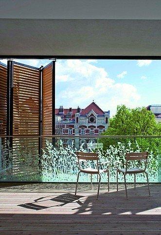 Überdachte Terrasse mit Geländer und stockwerkstiefen Faltschiebeläden zum Sonnenschutz. Bild: Werner Huthmacher