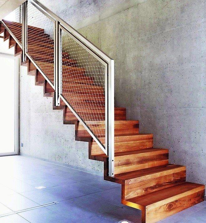 Holztreppe mit Edelstahlnetz als Treppengeländer.