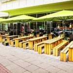 Außenbereich eines Restaurants mit Holzbänken und -tischen. Bild: Glatz AG
