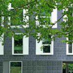 Dunkelgraue Hausfassade mit weißen Fensterrahmen und -läden. Bild: Roman Mensing