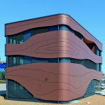 Auffallend ist die Fassadengestaltung mit teilweise gebogenen HPL-Platten, deren Maserung Holzstrukturen assoziieren. Bild: Horst Pütz