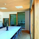 Konferenzraum mit prägenden Holzelementen an Decke und Pfosten-Riegel-Fassade aus Eichenholz innerhalb der Holz-Rahmen-Wände. Bild: Horst Pütz